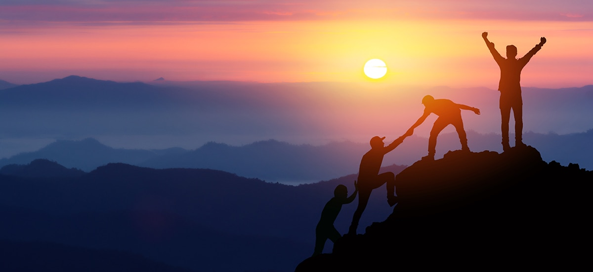 Group of people helping each other climb a mountain during sunset