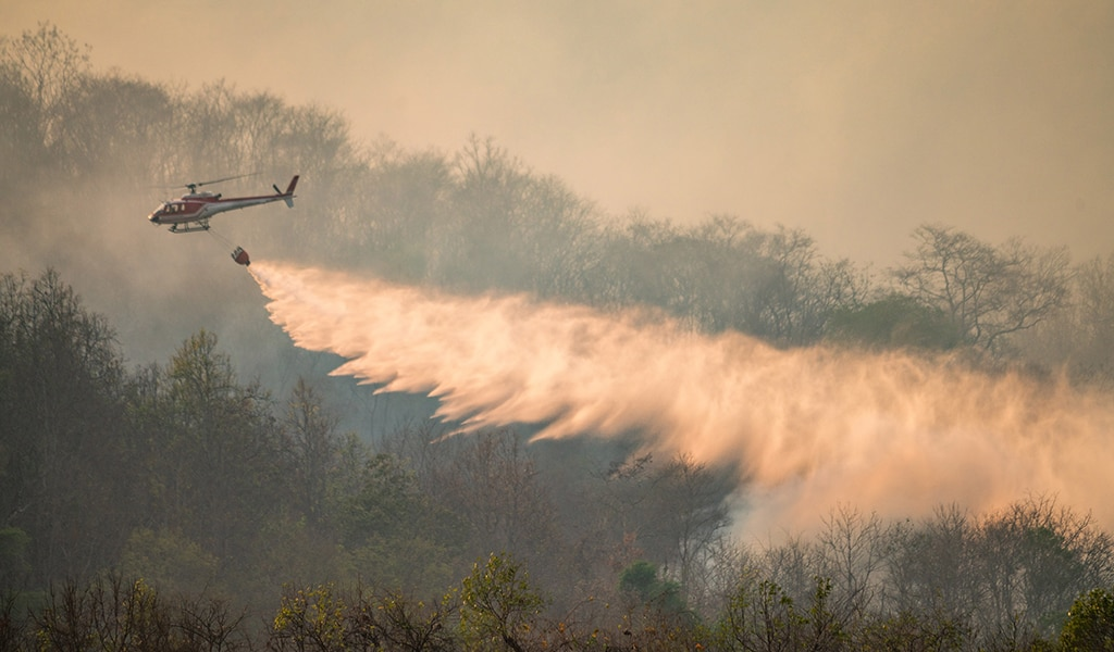 Helicopter spraying water on wildfire