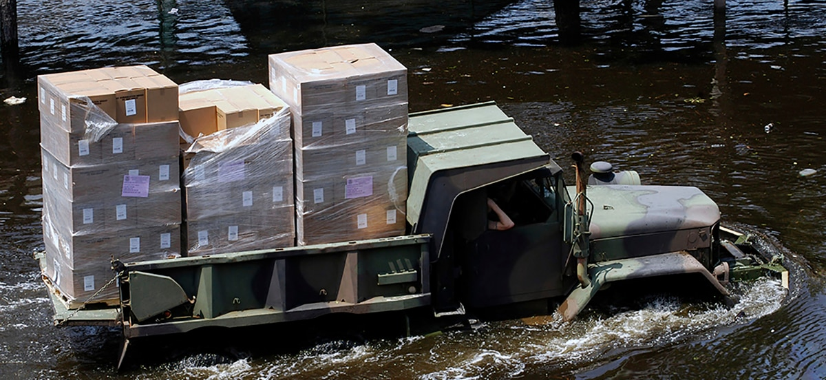 Army truck plows through flooded street bearing disaster relief supplies