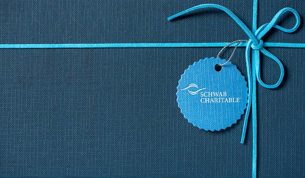 Blue gift with Schwab Charitable logo on the name tag