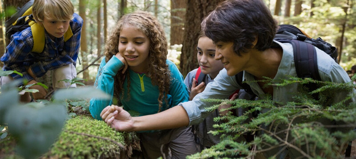 woman showing kids items during outdoor hike